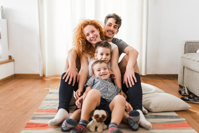 Eine Familie sitzt auf einem Teppich